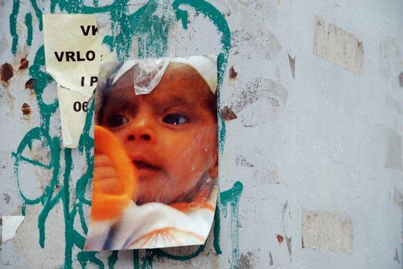 Ein Foto von Belmina Ibrisevic hängt an einer Hauswand. Das kleine Mädchen war der Auslöser für die Proteste gegen die bosnische Regierung.